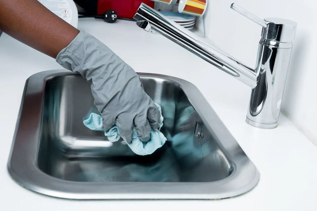 person cleaning sink